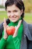微笑的逗人喜爱的妇女咬住成熟苹果 免版税库存照片