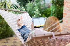 Женщина используя планшет пока ослабляющ в гамаке Стоковая Фотография