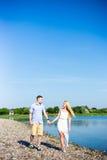 暑假概念-走在海滩的年轻夫妇 库存图片