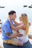 年轻美好的夫妇坐多岩石的海滩 免版税图库摄影