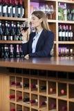 嗅到红葡萄酒的中间成人顾客反对架子 免版税库存照片