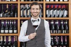拿着红葡萄酒的侍酒者玻璃反对架子 图库摄影