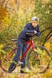 青少年在红色自行车 免版税库存图片