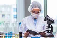 年轻学生与化工解答一起使用在实验室 免版税库存照片