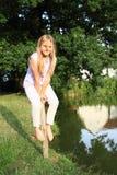 女孩坐柱子由河 库存图片