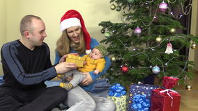 Жизнерадостный подарок семьянина и женщины присутствующий для младенца в рождестве сток-видео