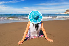 Γυναίκα στο καπέλο που απολαμβάνει τις διακοπές ήλιων στην παραλία Στοκ Φωτογραφία