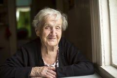 年长妇女微笑的坐在桌上 愉快 库存照片