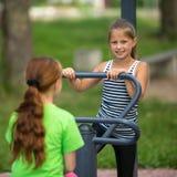 哄骗女孩在公开运动器材的实践体操 免版税库存照片
