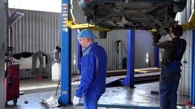 Потревоженный механик обсуждая ситуацию на проблемах ремонта автомобиля видеоматериал