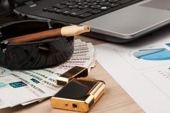 运转的商人书桌、打火机和膝上型计算机、雪茄和金钱 库存图片
