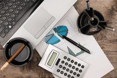 运转的商人书桌、膝上型计算机、雪茄和图作为背景 库存图片