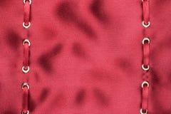 在红色丝绸的金戒指插入的红色缎丝带 免版税库存图片