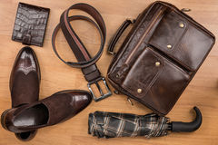 经典棕色鞋子、公文包、传送带和伞在木地板上 免版税库存照片