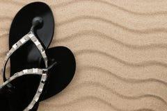 使黑触发器靠岸复与站立在沙子的假钻石 免版税图库摄影