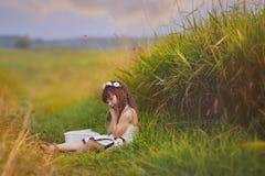 放松在草的女孩 免版税库存图片