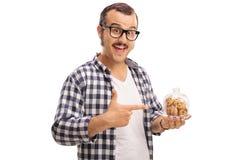 拿着一个瓶子曲奇饼的人 免版税库存照片