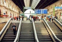 Большая зала железнодорожного вокзала и много людей ждать прибытие поезда Стоковая Фотография