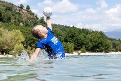 拿到一个球的男孩在湖 库存照片