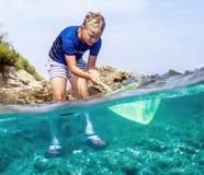 Αγόρι με το δίχτυ του ψαρέματος που η παράκτια φύση Στοκ Φωτογραφία