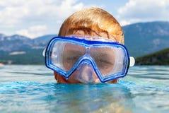 有水肺面具的男孩在湖 免版税图库摄影