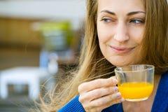 Η νέα όμορφη γυναίκα απολαμβάνει το φλυτζάνι του τσαγιού Στοκ Φωτογραφία