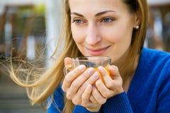 Η νέα όμορφη γυναίκα απολαμβάνει το φλυτζάνι του τσαγιού Στοκ εικόνες με δικαίωμα ελεύθερης χρήσης