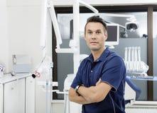Βέβαιος οδοντίατρος τα όπλα που διασχίζονται με στην κλινική Στοκ Εικόνες