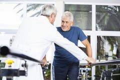Ανώτερο άτομο που εξετάζει το γιατρό περπατώντας στο στούντιο ικανότητας Στοκ Εικόνες
