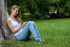 детеныши женщины чтения парка книги Стоковые Фотографии RF