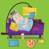Человек лежа на софе с много устройств Стоковое Изображение