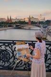 Женщина красит ориентир ориентиры города на вечере Стоковое фото RF