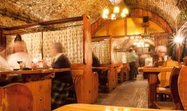 见面为晚餐的老年人在有砖墙的古板的餐馆 库存图片