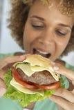 吃中间妇女的成人汉堡 免版税库存图片