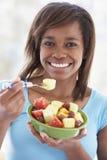 吃新鲜水果少年女孩的沙拉 免版税图库摄影