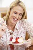 吃中间妇女的成人乳酪蛋糕 免版税库存照片