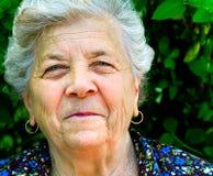 使老一名高级微笑妇女满意 免版税库存照片