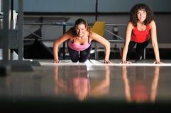 二名妇女在健身俱乐部解决 库存图片