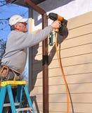 安装人钉子房屋板壁的枪 免版税库存图片