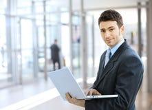 компьтер-книжка бизнесмена используя Стоковые Изображения