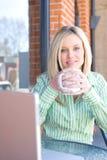 企业咖啡馆坐的妇女工作 免版税图库摄影