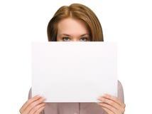 女孩隐藏的纸俏丽的页下 免版税图库摄影