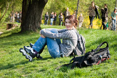 女孩公园休息的溜冰者 库存图片