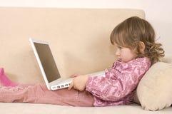使用年轻人的女孩膝上型计算机 免版税库存图片