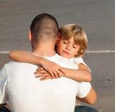 男孩父亲他拥抱的年轻人 免版税库存图片