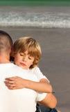 男孩父亲他拥抱的年轻人 免版税库存照片