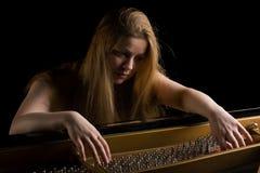 在女孩大平台钢琴之后 库存图片