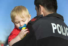 младенец держит полиций офицера Стоковая Фотография