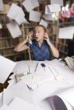 女实业家飞行她的办公室纸张页 免版税库存照片