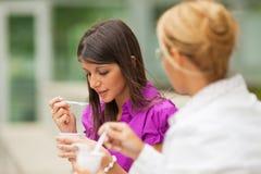 吃酸奶的女实业家 免版税库存图片